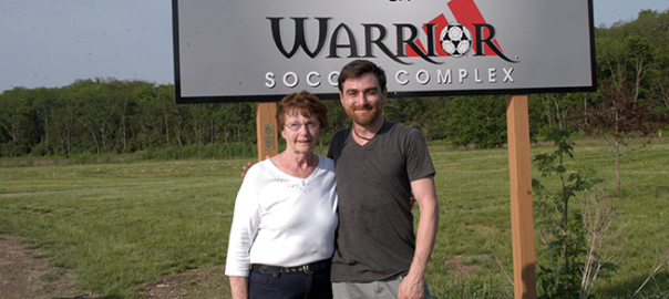 Carol Maas and Michael Blackwell standing in front of the Hank and Carol Maas Warrior Soccer Complex in Dayton Ohio